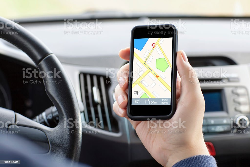 man in the car holding a phone with interface nav stock photo