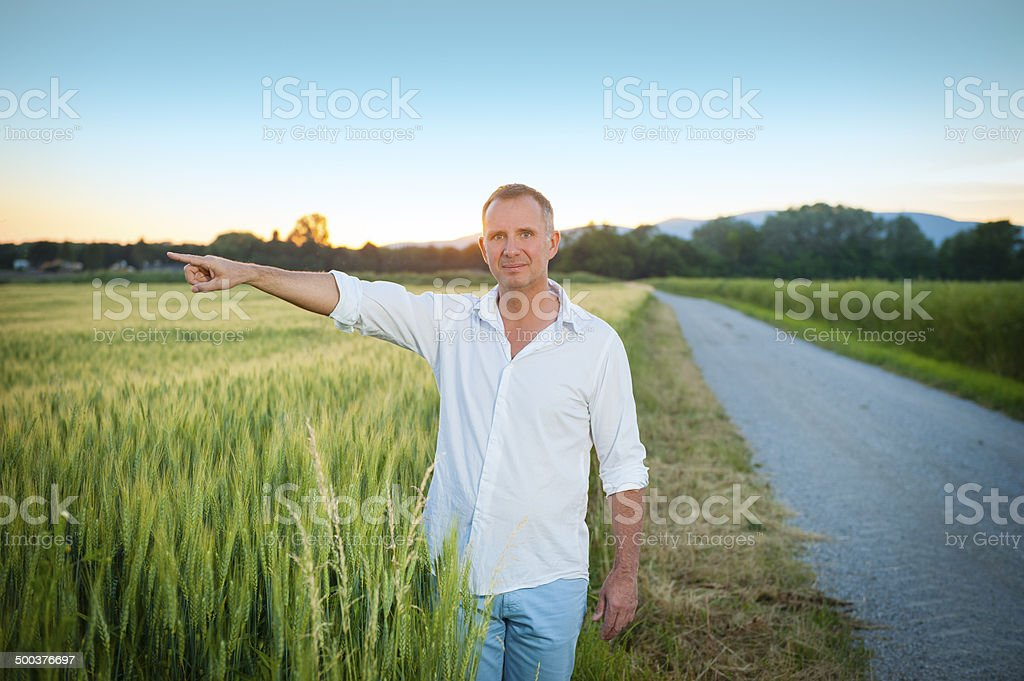 Man in the field pointing left royalty-free stock photo