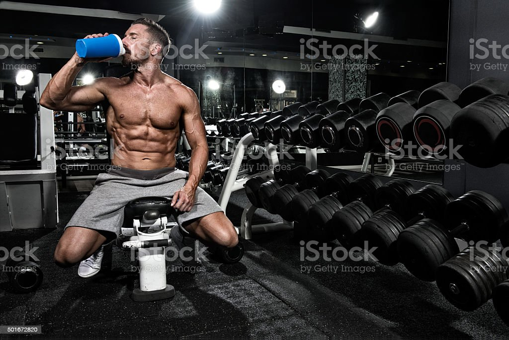 Man in the gym drinking protein shake drink stock photo