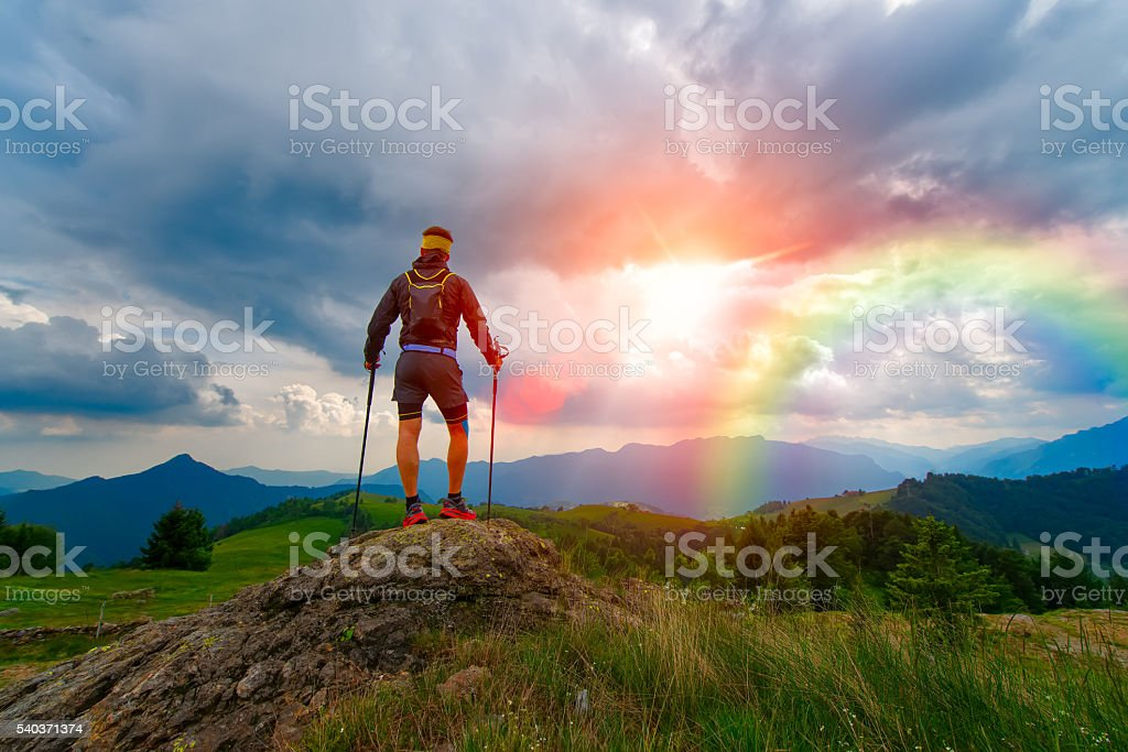 Man in the mountains at sunset with rainbow stock photo