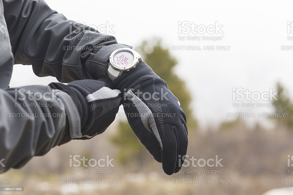 Man in the mountains checking his current Suunto wrist watch royalty-free stock photo