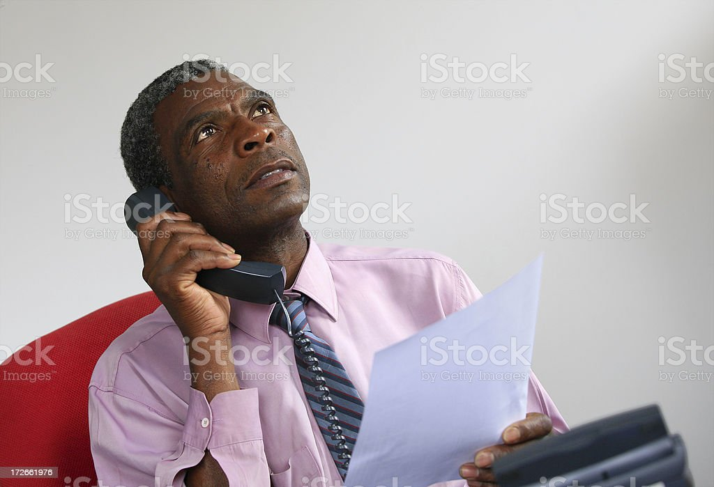 \'A greying African man in a tie, holding a document and speaking on...