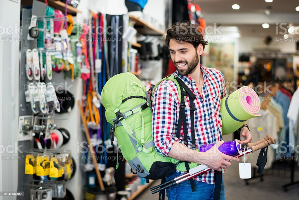 Man in the store buying camping equipment stock photo
