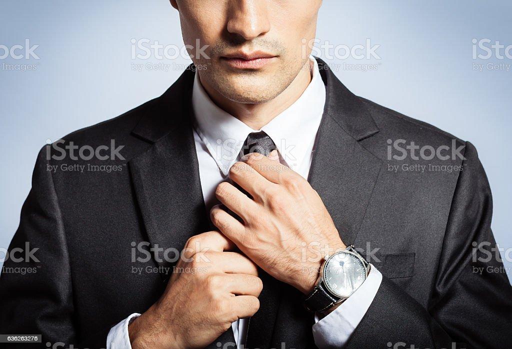 Man in the suit fixing his tie stock photo