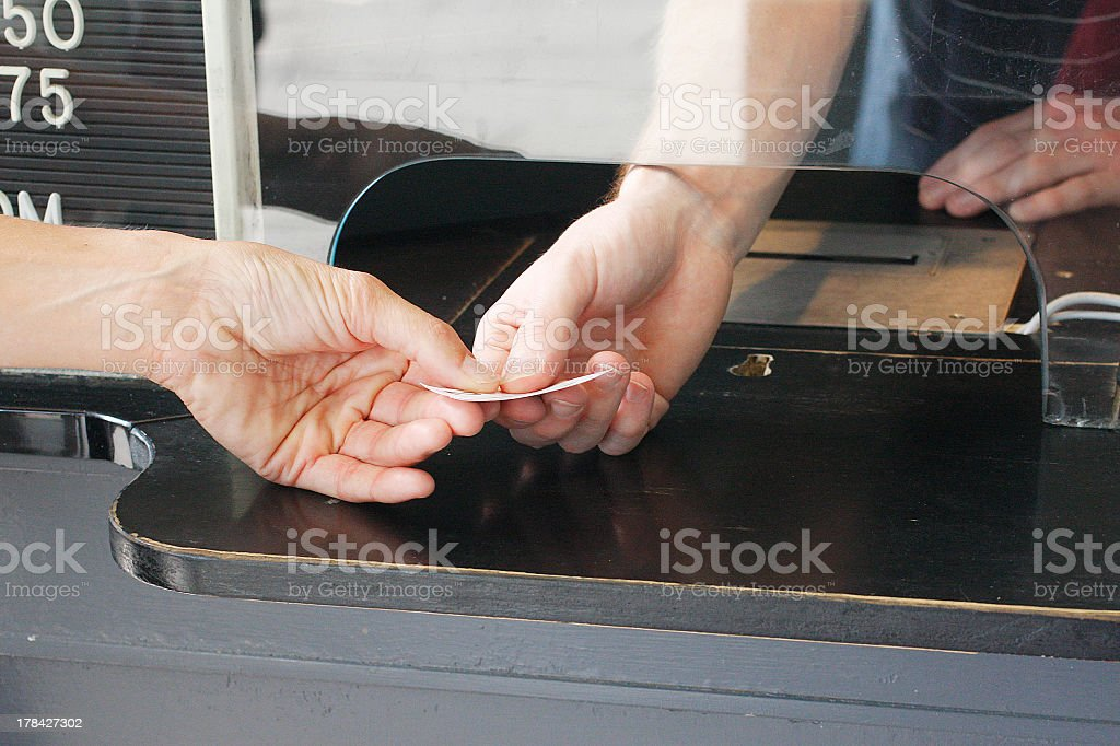 Man in ticket booth handing ticket to customer stock photo