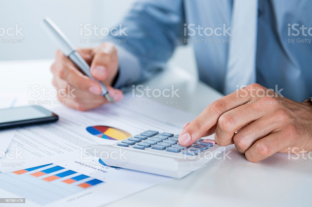 Man in tie using calculator at desk with graphs stock photo