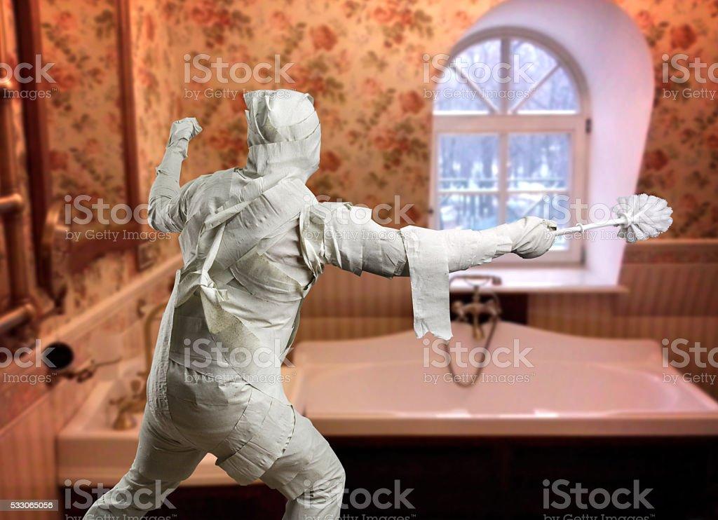Man in toilet paper with toiletbrush stock photo