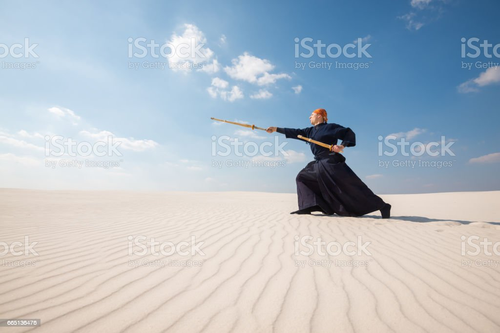 Man in traditional clothes makes a powerful lunge with a training sword stock photo