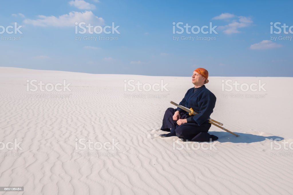Man in traditional clothes meditates during the practice of martial arts stock photo