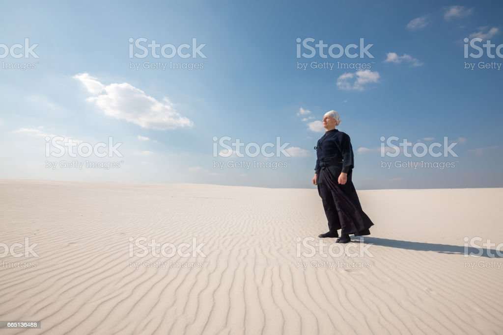 Man in traditional clothes stands and meditates in the middle of desert stock photo