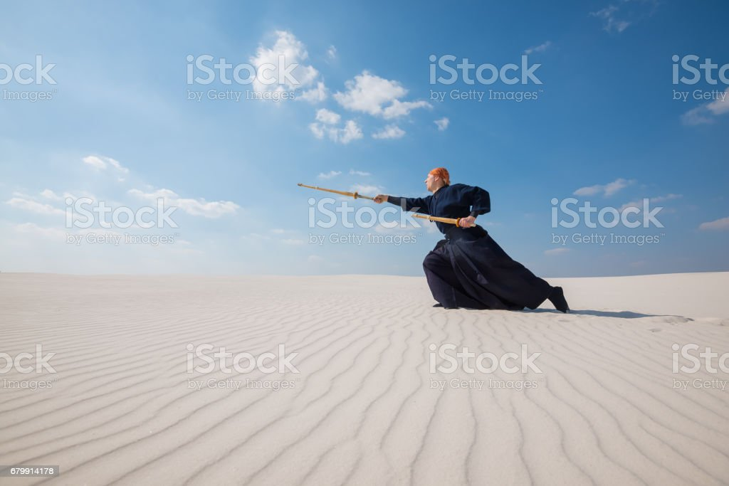 Man in traditional Japanese clothes makes a deep lunge with a shinai stock photo