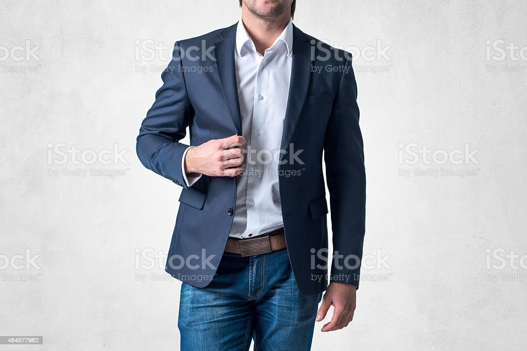 Man in trendy suit  standing alone holding his jacket with stock photo