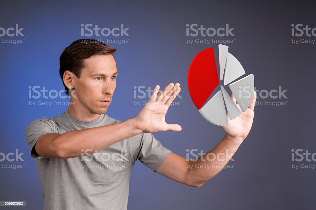 Man in t-shirt working with pie chart on blue stock photo