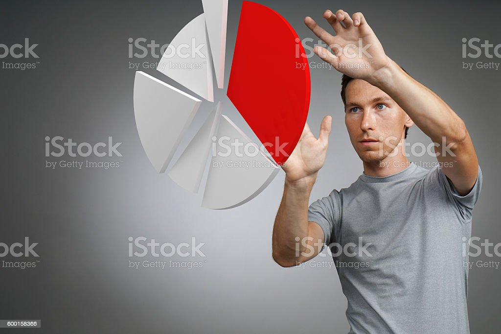 Man in t-shirt working with pie chart on grey stock photo