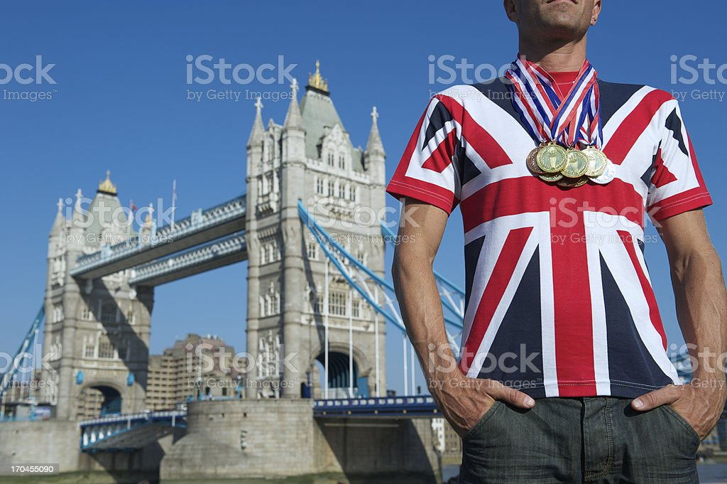 Man in Union Jack Stands at Tower Bridge with Medals royalty-free stock photo