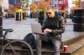 Man in urban environment using laptop