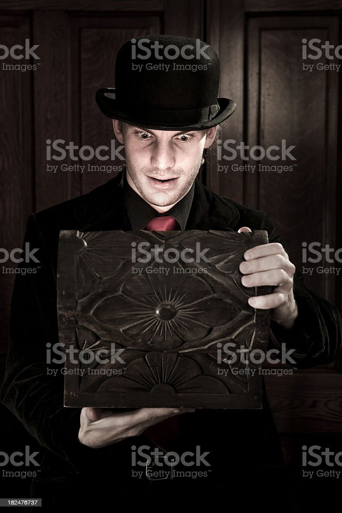 Man in vintage bowler hat opening wooden treasure box stock photo