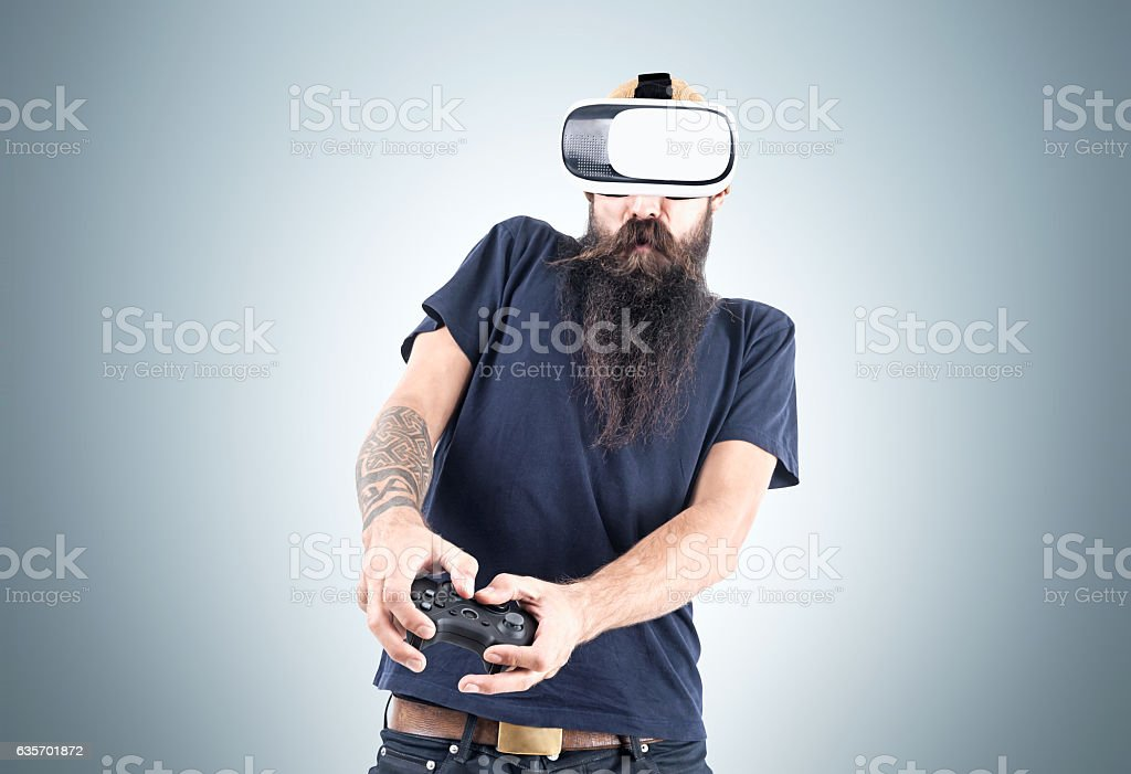 Man in vr glasses near a gray wall stock photo