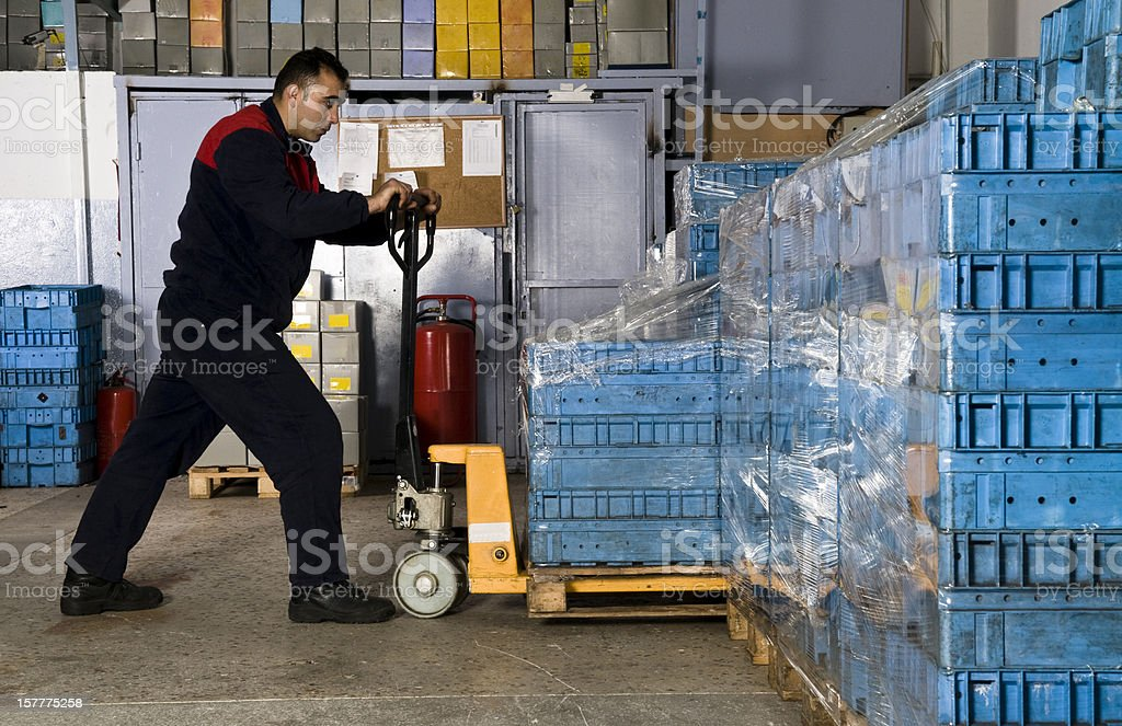 Man in warehouse pulling shipping crate. royalty-free stock photo
