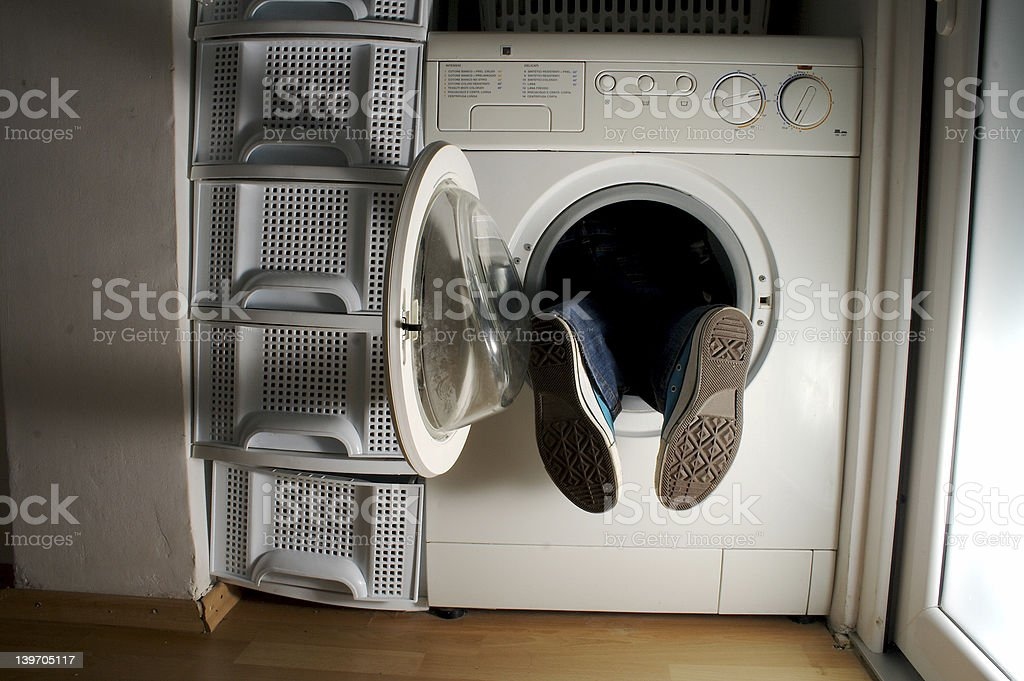 Man in washing machine with 2 feet sticking out stock photo