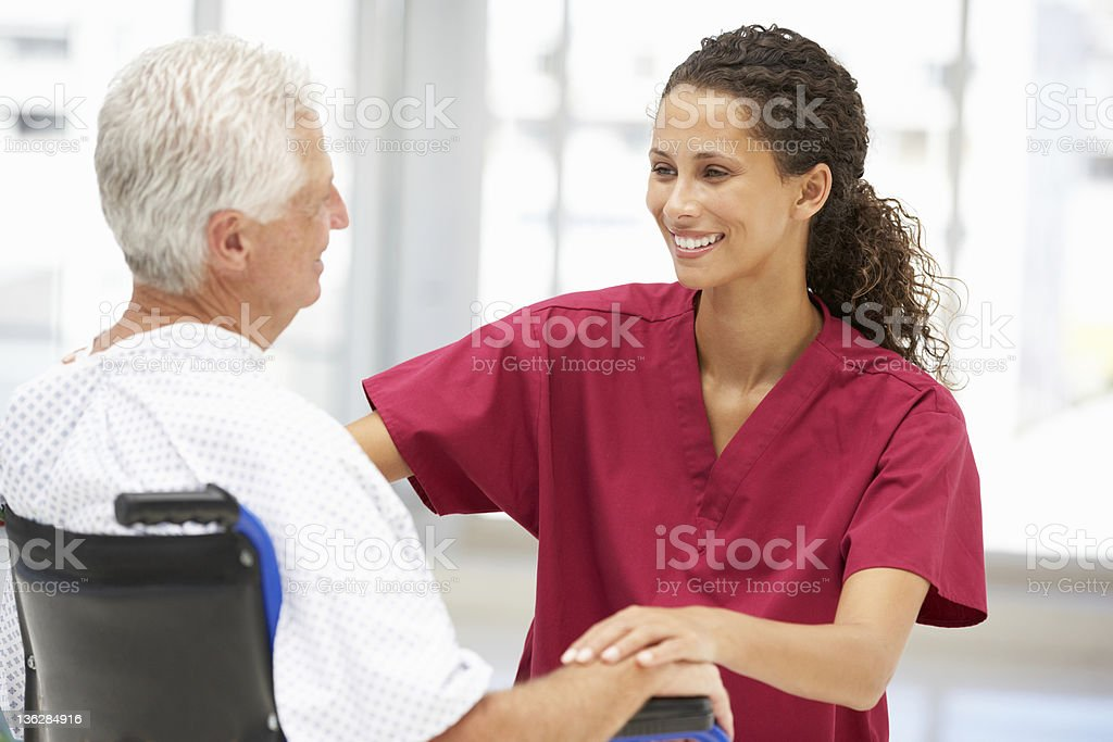Man in wheelchair being assisted by healthcare provider royalty-free stock photo
