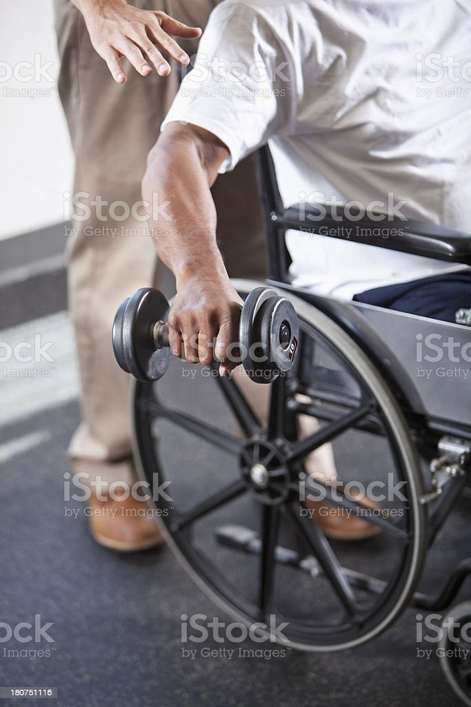 Man in wheelchair doing physical therapy exercises royalty-free stock photo