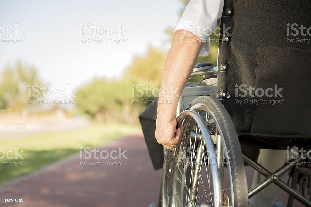 Man in wheelchair going down the sidewalk stock photo