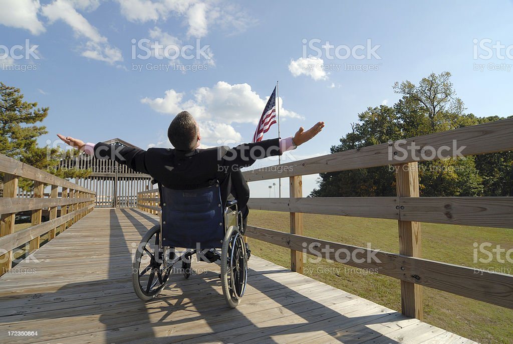 Man in Wheelchair Outstretches Arms Before American Flag royalty-free stock photo