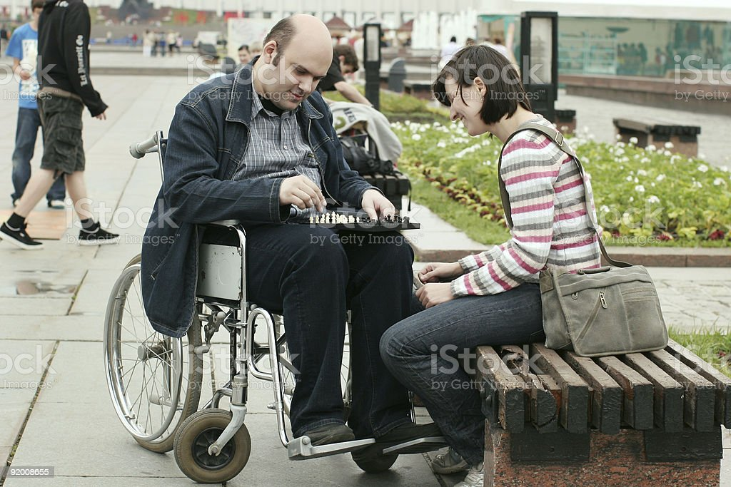 Man in wheelchair playing chess with a woman in park royalty-free stock photo