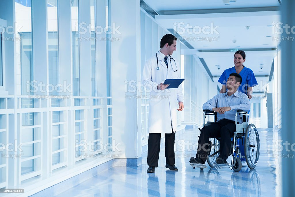 Man in wheelchair talking to his doctor and nurse stock photo