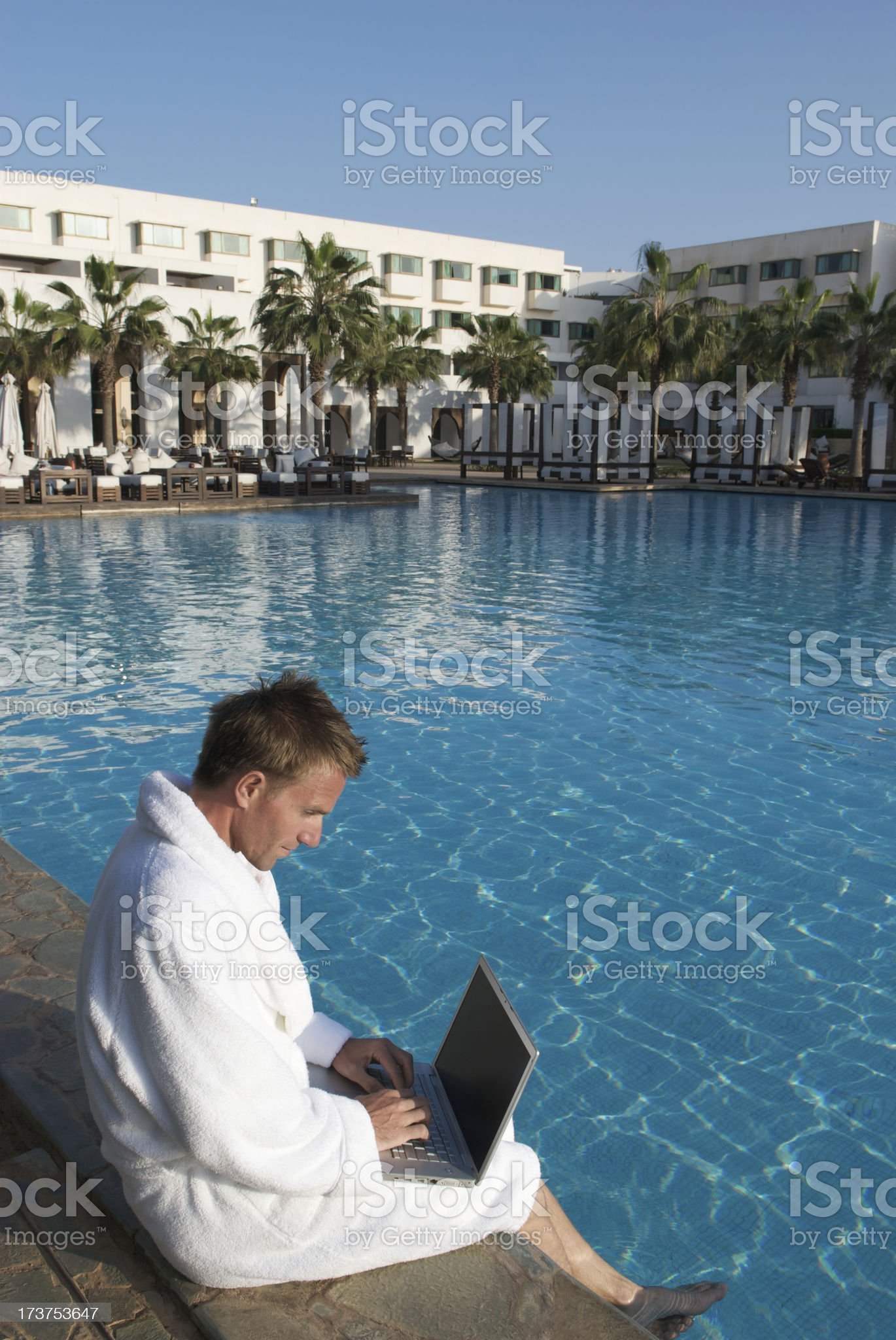 Man in White Bathrobe Relaxes with Laptop at Resort Pool royalty-free stock photo