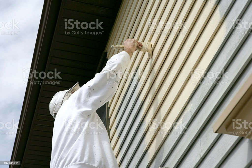 Man in white coveralls painting the outside of a house stock photo