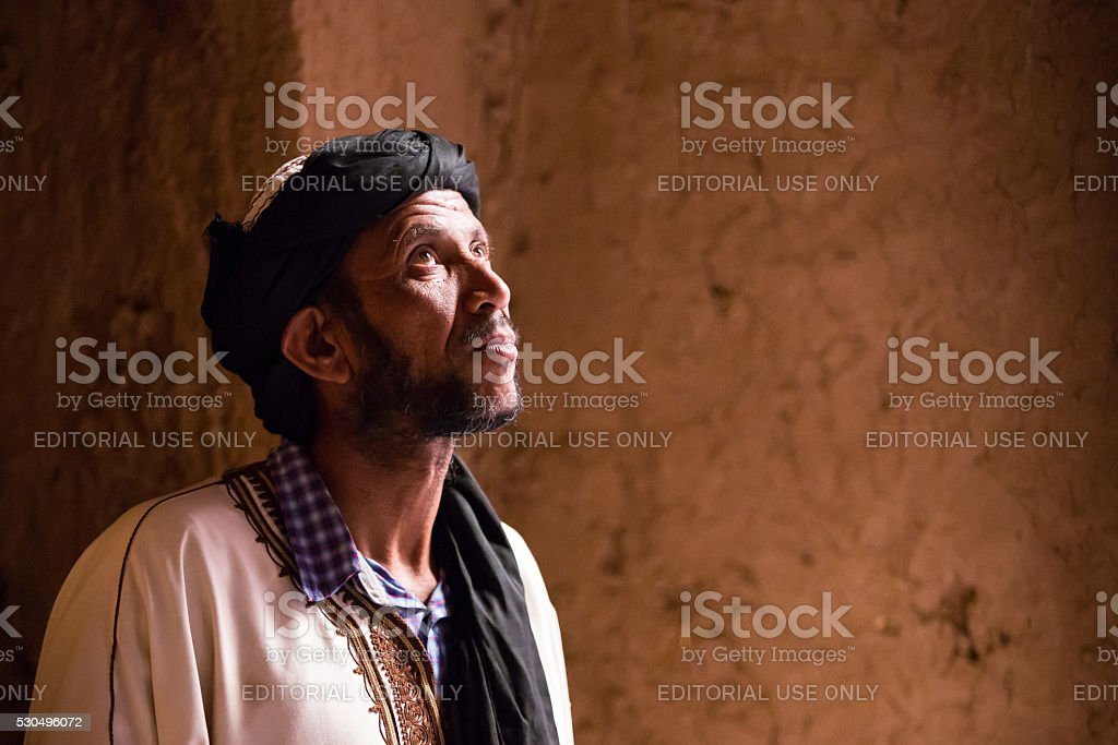 man in white dress posing in kasbah stock photo