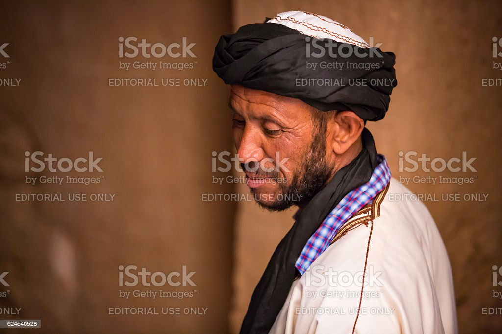 man in white dress posing in kasbah stock photo