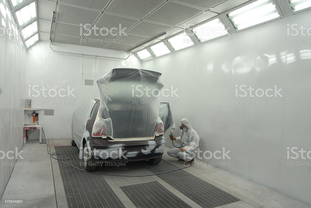 Man in white garage painting automobile stock photo