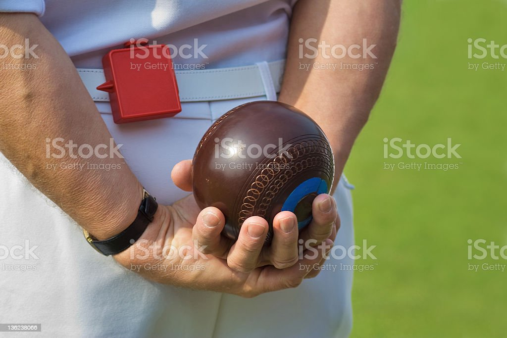A man in white holding lawn bowls behind his back stock photo