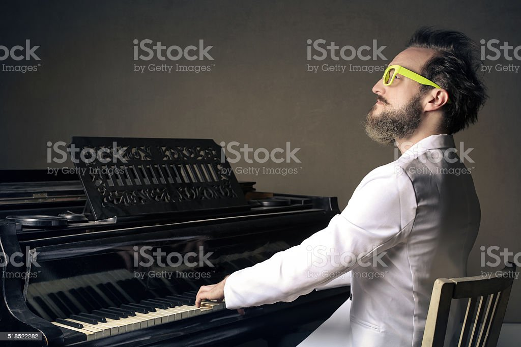 Man in white playing a piano stock photo