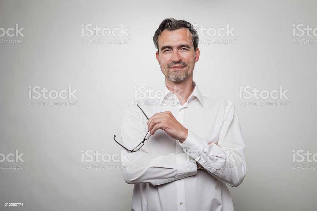man in white shirt crosses his arms holding glasses stock photo