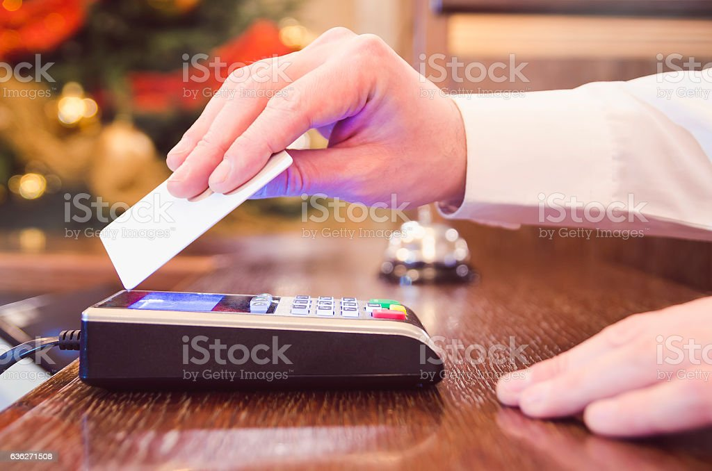 Man in white shirt paying bill with contactless credit card. stock photo