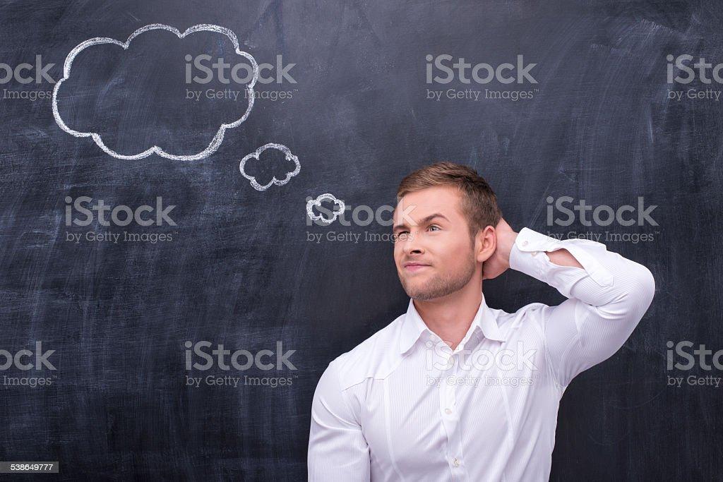 Man in white shirt thinking hard stock photo