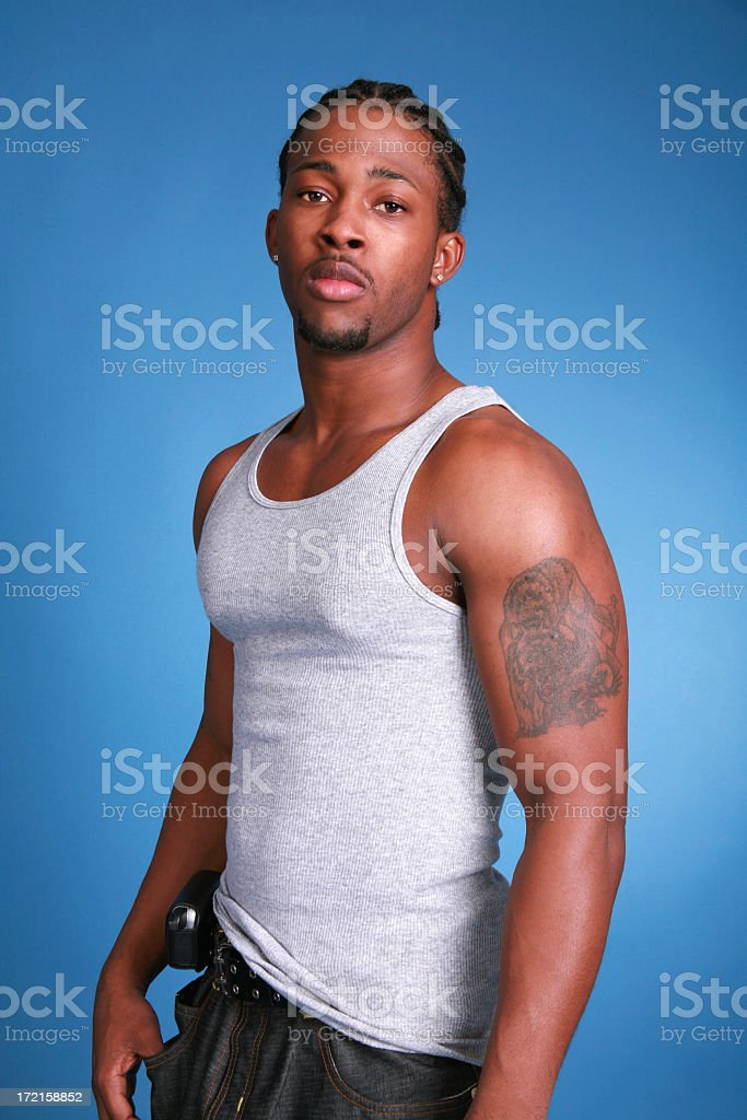 Man in white tank top with tattoo on arm in bad boy pose stock photo