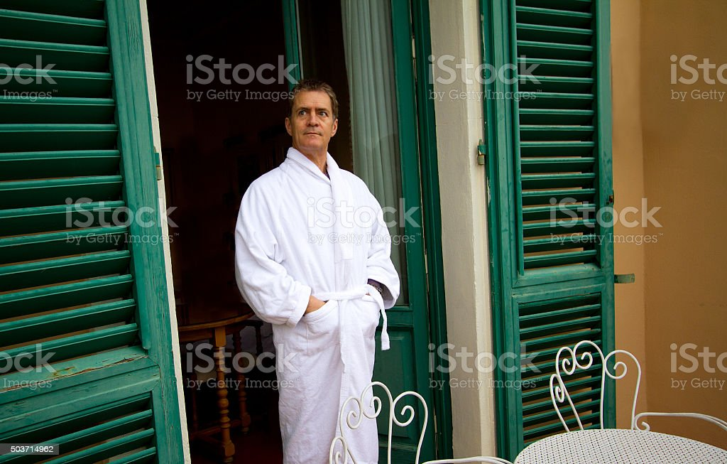 Man in White Terrycloth Bathrobe at Window with Green Shutters stock photo