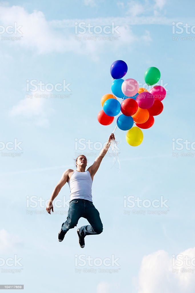 Man in white vest and jeans flying with multicolor balloons royalty-free stock photo