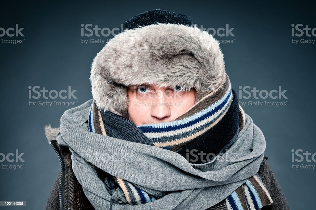 Man in winter clothes is tightly bundled up, cap, scarves stock photo