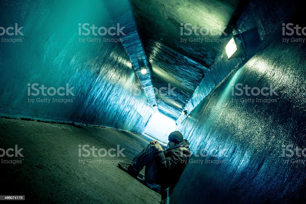 Man in winter clothing huddled in a concrete tunnel stock photo