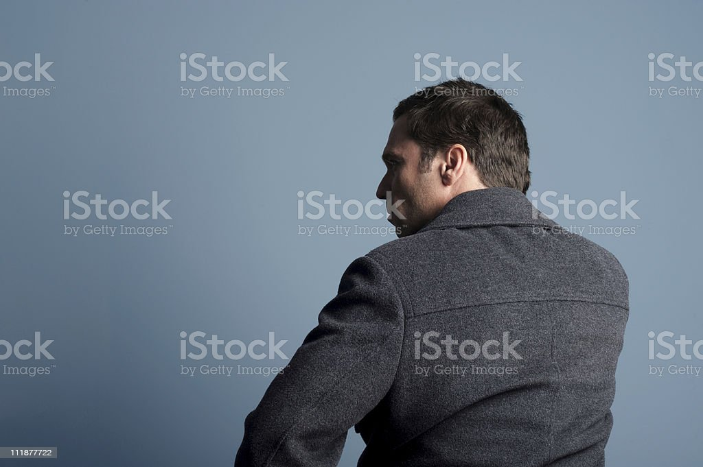 Man in Winter Coat against Blue Gray Wall From Behind royalty-free stock photo
