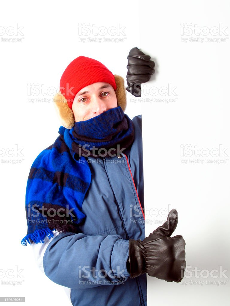 Man in Winter Gear Holding Blank Sign, Giving Thumbs-up Gesture royalty-free stock photo