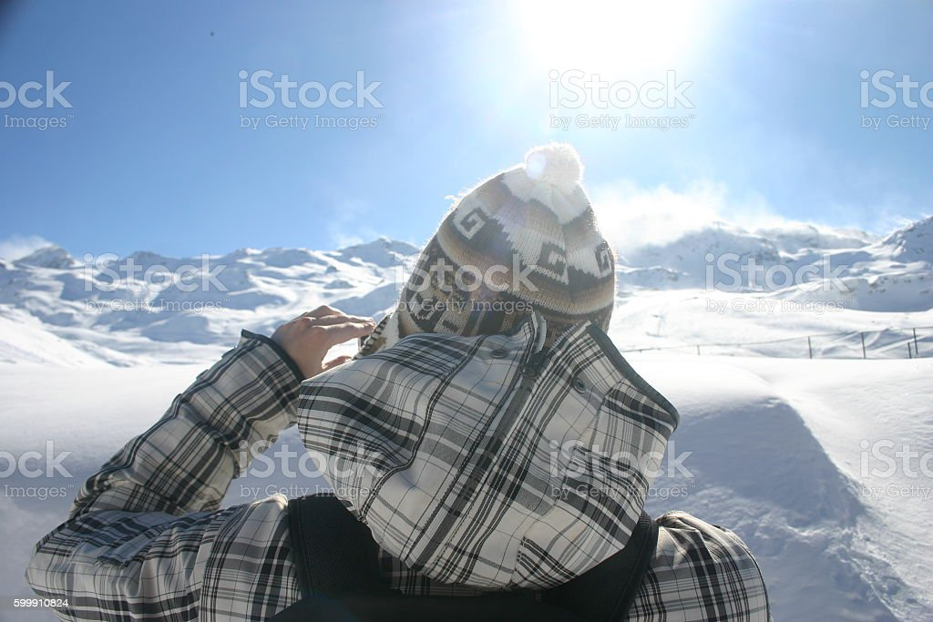 Man in winter jacket looking at snowy mountains far off stock photo