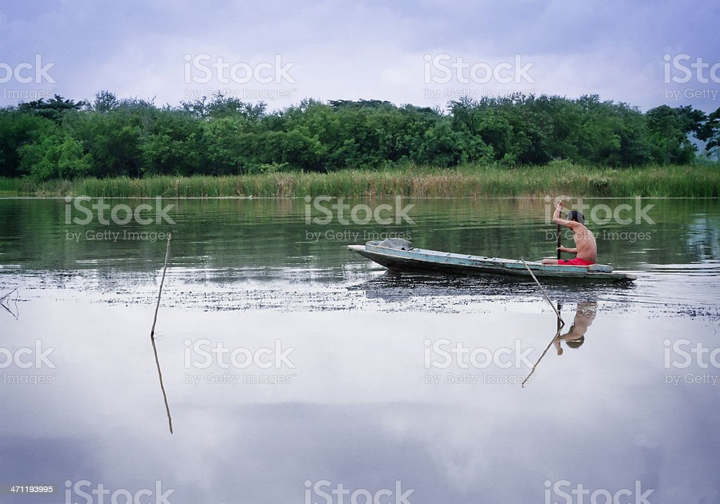 Man in wooden boat paddling up a river in Thailand stock photo