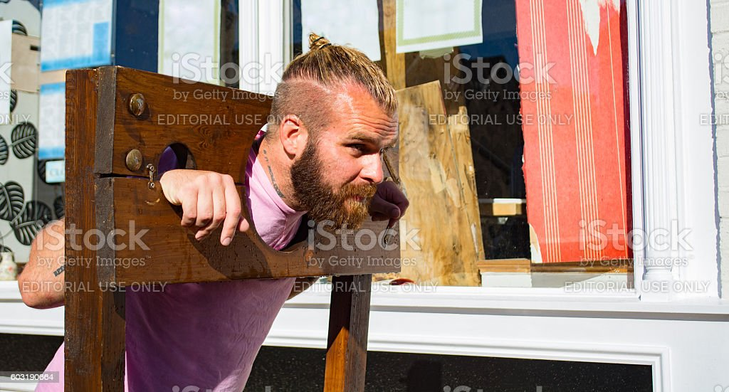 Man in Wooden Stocks stock photo